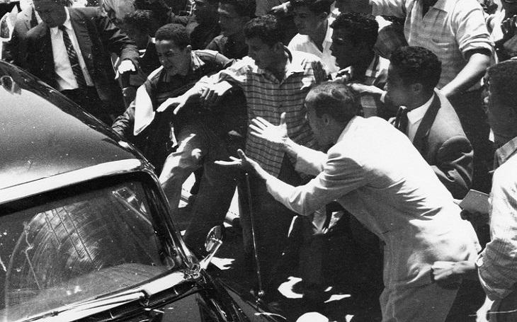 VIDEO: Drsné přivítání Richarda Nixona ve Venezuele. Bušení pěstmi, házení kamenů, plivance. Viceprezidentská kolona pod palbou